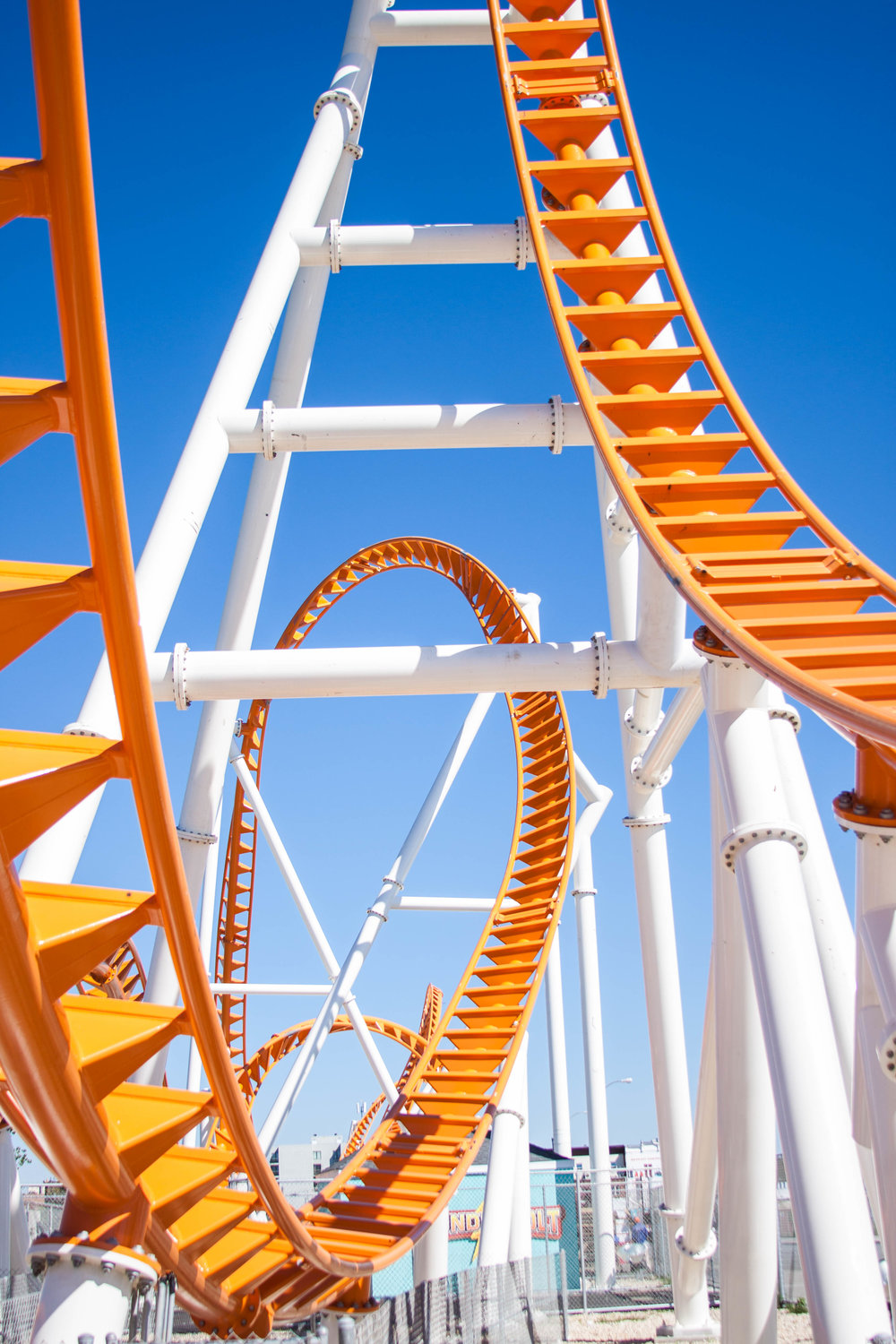 Orange tracks attached to the white support structure that makes up the Thunderbolt Roller Coaster in Brooklyn's Coney Island. MEP designed by 2LS Consulting Engineering.