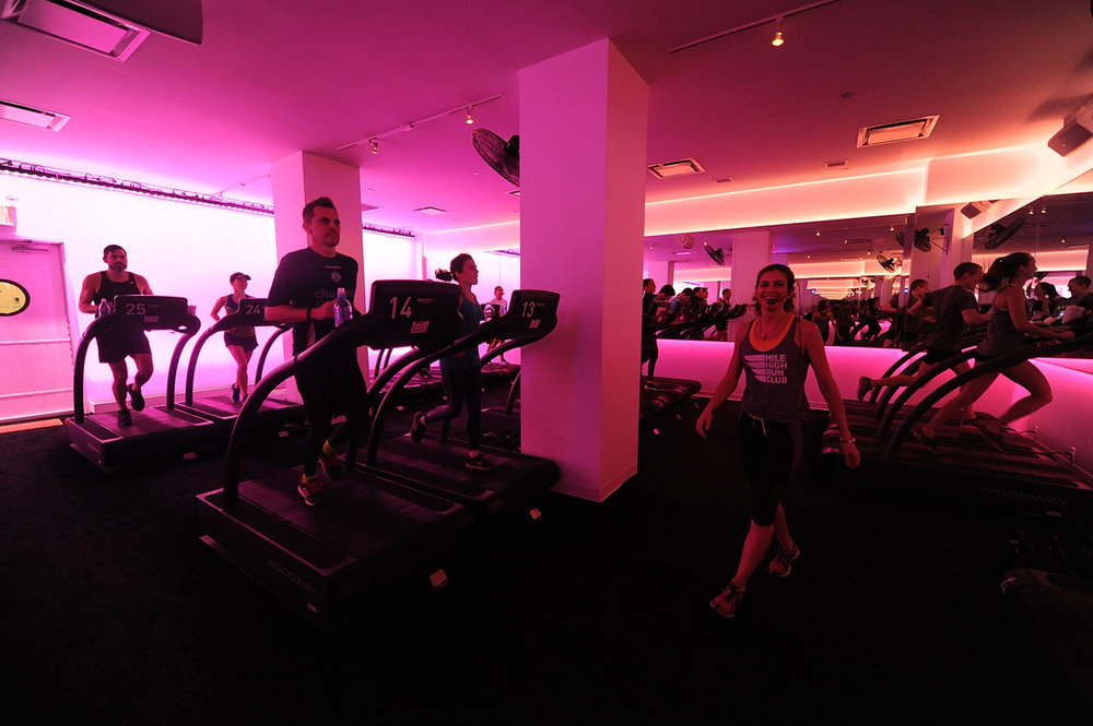 Fitness instructor leading a class as people run on various treadmills in a pink lit studio at the Mile High Run Club in New York, with MEP designed by 2LS Consulting Engineering.