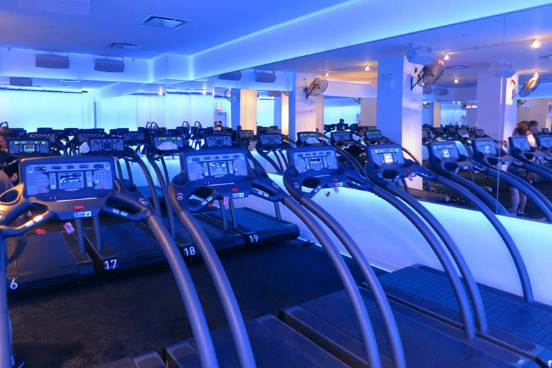 A running studio at the Mile High Run Club with accented blue lighting and rows of treadmills for clients. MEP provided by 2LS Consulting Engineering.