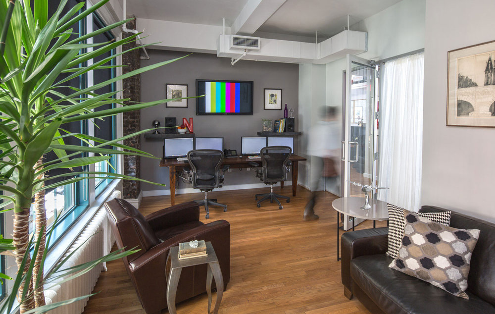 Man leaving an office space with lounge area and multiple monitors, including one showing vertical color bars in the studio of Napoleon. MEP designed by 2LS Consulting Engineering.