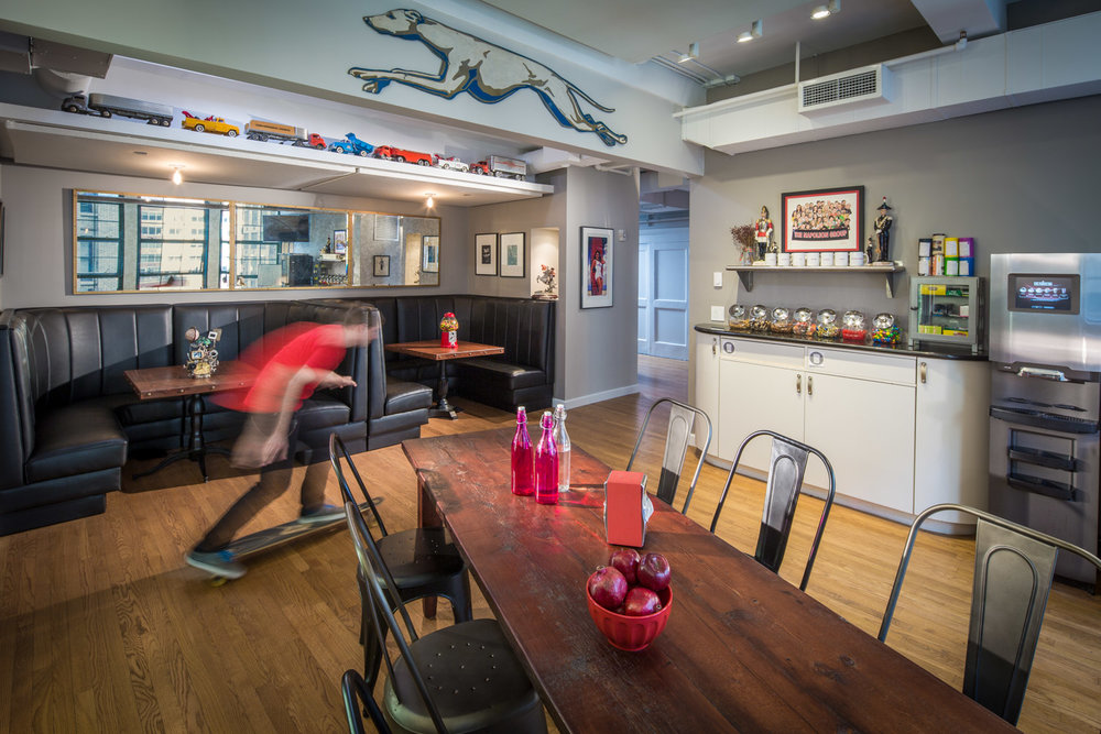 Man in red shirt skateboards through booths at the playfully decorated kitchen of Napoleon studios in Brooklyn, New York. MEP designed by 2LS Consulting.