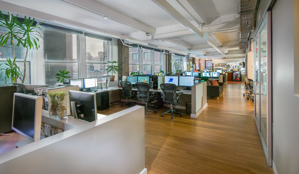 Cubicle spaces with various computers and plants along the windows of the Napoleon studios in Brooklyn, New York. MEP provided by 2LS Consulting Engineering.