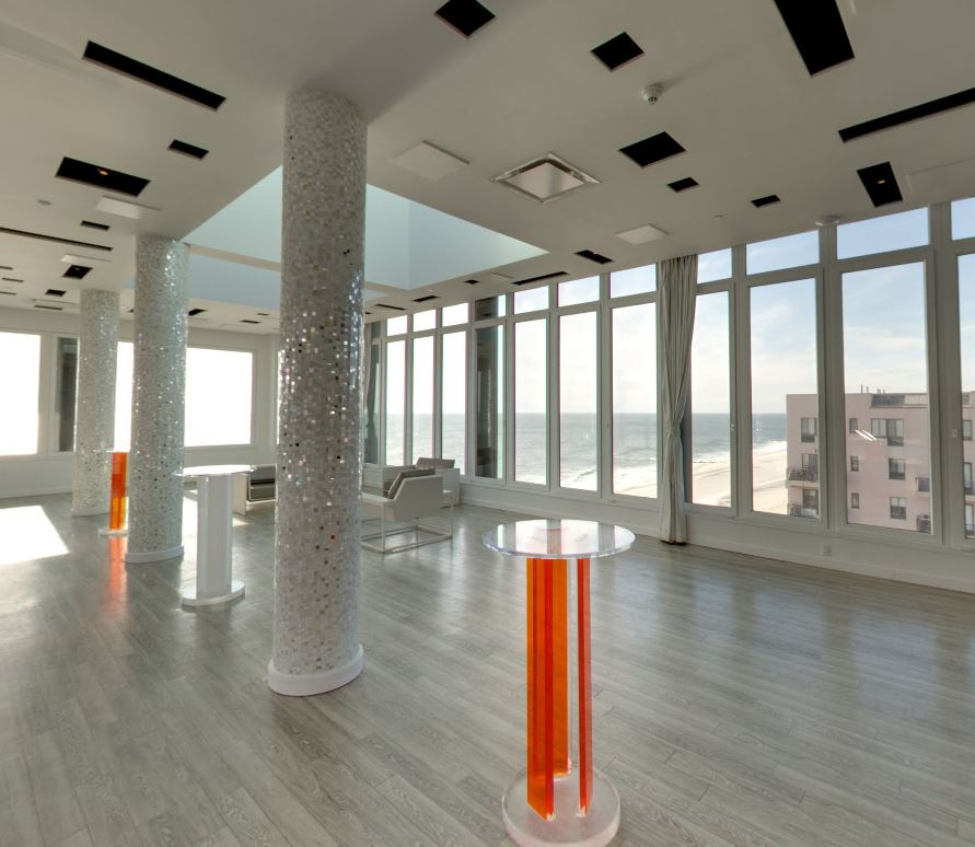 Large event space with a bar and modern furniture, mosaic columns, and large windows overlooking Long Beach, New York. MEP for the Allegria Hotel designed by 2LS.