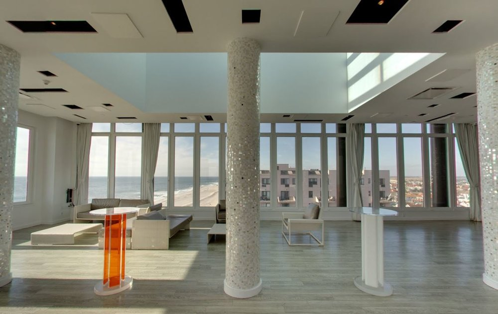Upstairs bar lounge area at the Allegria Hotel, with modern furniture, mosaic columns, and large windows and skylights. MEP designed by 2L Engineering..