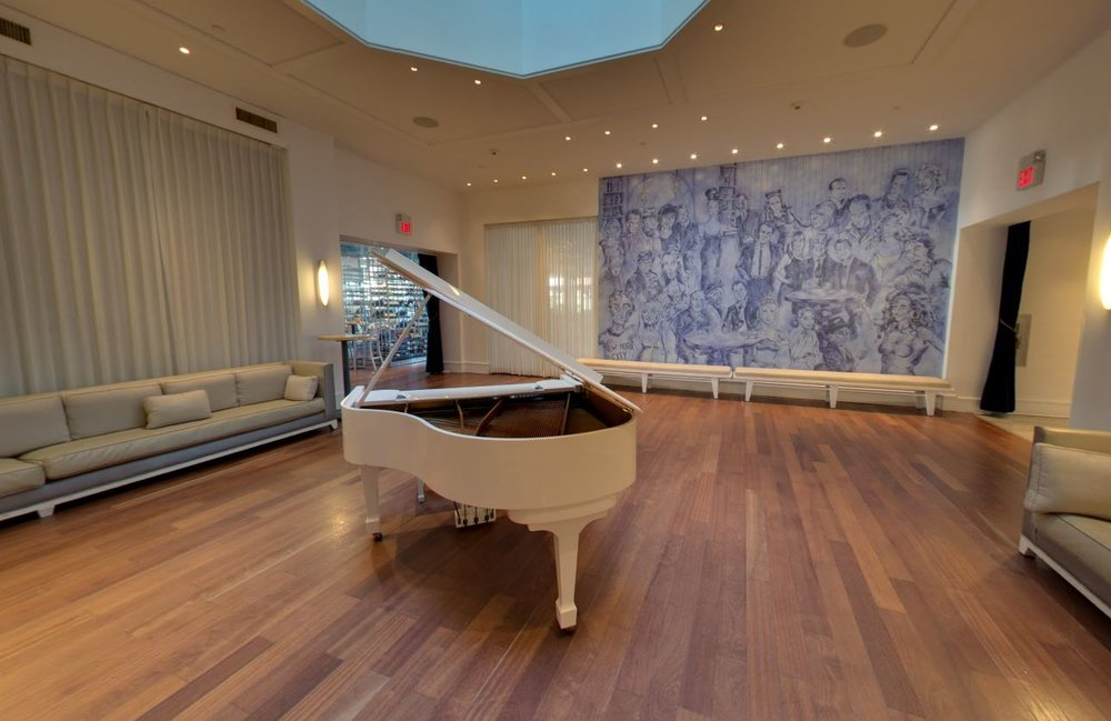 White grand piano on wood panel flooring and a bench under a large mural featuring caricatures of people in tones of blue. MEP designed by 2LS Consulting.