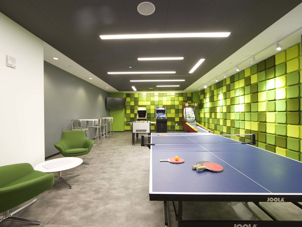 Pink pong table, arcade games, skee-ball, and foosball in the in the green accented rec room of Rocketfuel headquarters. MEP by 2L Engineering.