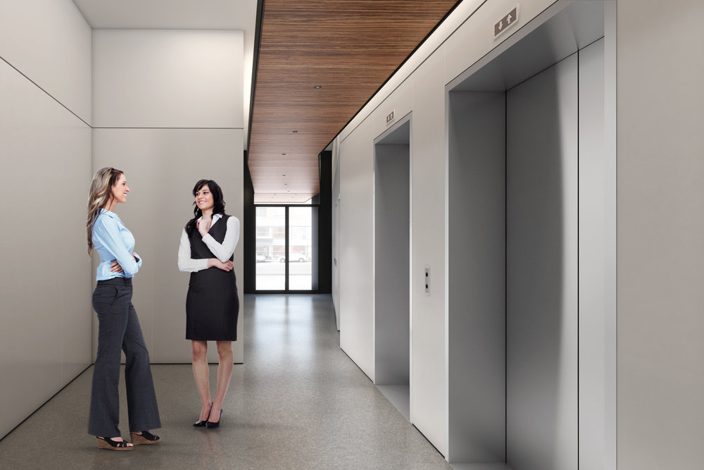 Two smiling women having a conversation as they wait for the elevator in the lobby of Atlas Capital. MEP provided by 2LS Consulting Engineering.