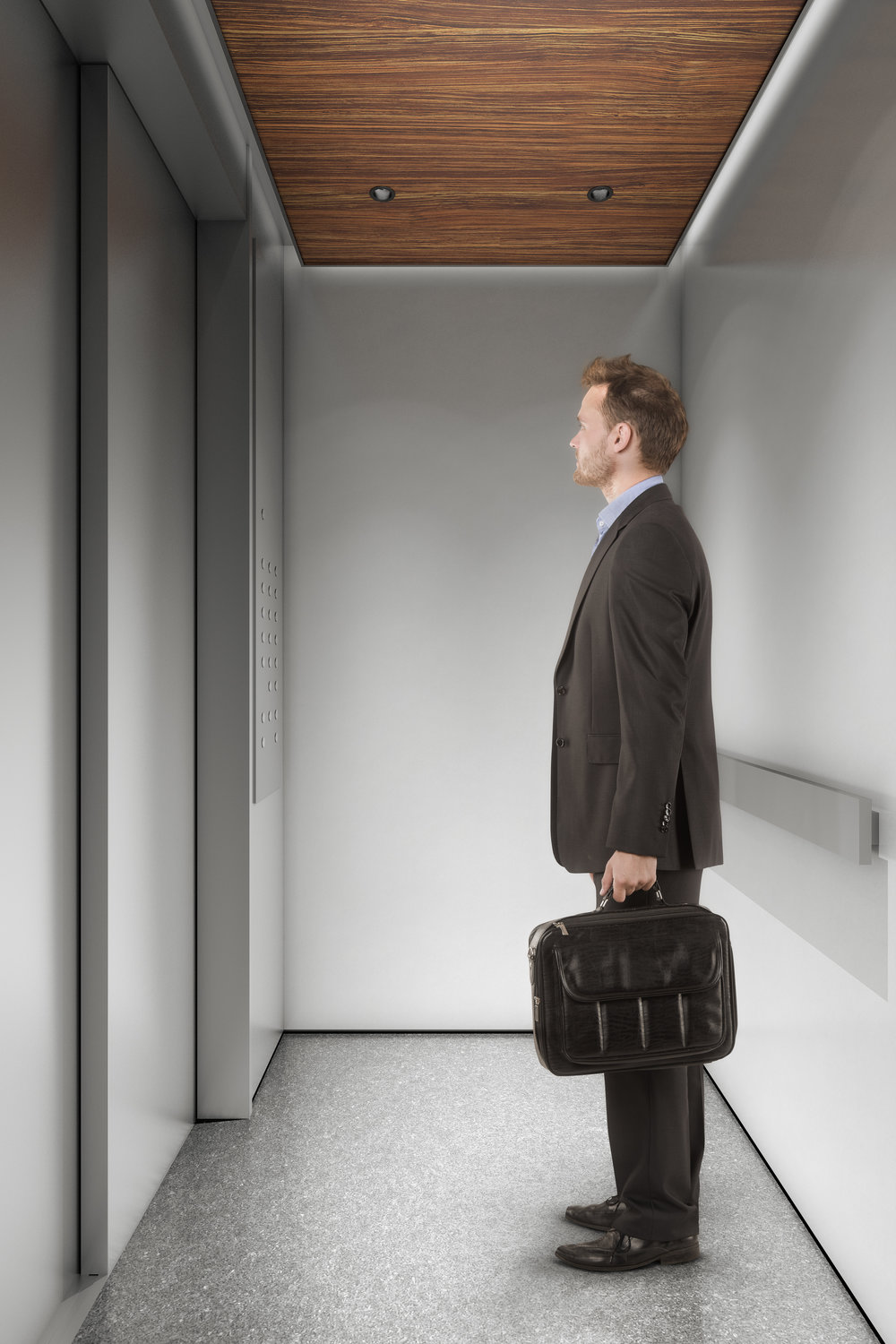 Man staring at the elevator doors as he waits to arrive on the right floor. MEP provided by 2L Engineering.