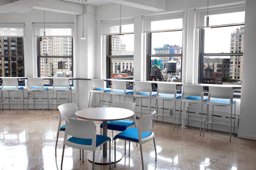 Blue and white chairs in Publishers Clearing House office's lounge area facing the New York City skyline. MEP provided by 2LS Consulting Engineering.