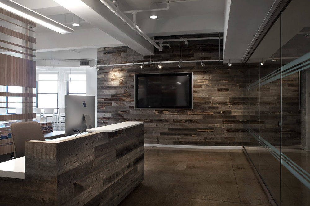 Reception area with wood accent panelled walls and desk at the office of Publishers Clearing House. MEP provided by 2LS Consulting Engineering.