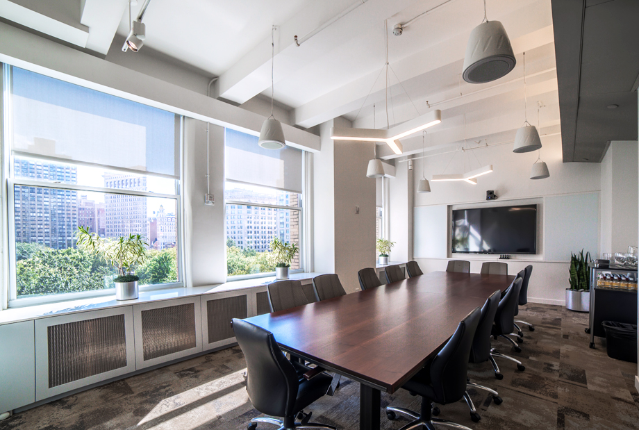 Conference room overlooking greenery with large windows and plants on the windowsill. MEP provided by 2LS Consulting Engineering.