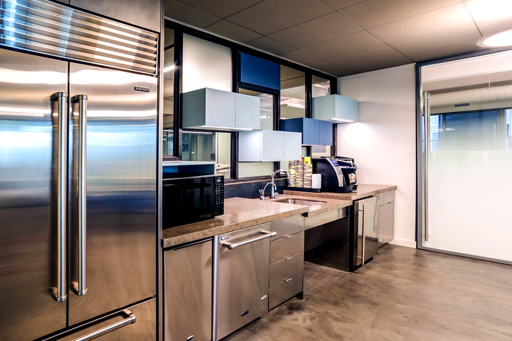 Kitchenette designed with hovering cabinets in different shades of blue in the offices of Rockrose. MEP designed by 2LS Consulting Engineering.