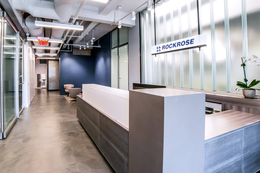 Reception area of Rockrose with minimalistic, modern design and the company's name featured above the desk. MEP designed by 2LS Consulting Engineering.