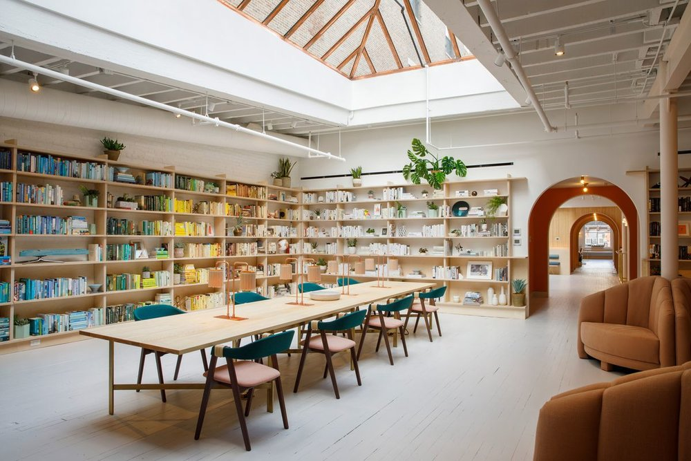 Colorfully organized bookcase and a table to work and collaborate in women's social club, The Wing Soho, New York. MEP by 2L Engineering.