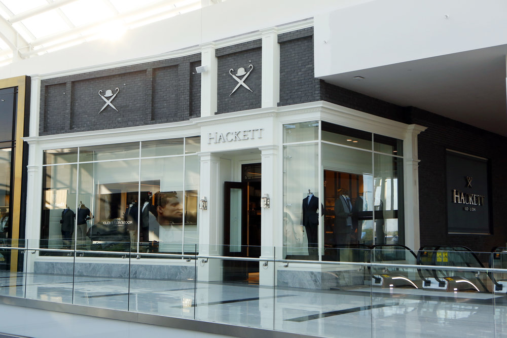 Stylish and chic window display of Hackett London's retail store with the bowler hat and two umbrellas logo over the display. MEP designed by 2LS Consulting Engineering.
