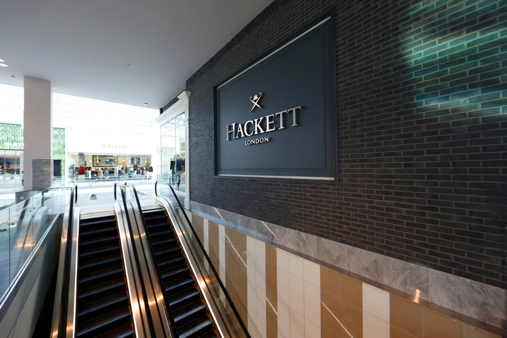 Hackett London's signage against a brick wall by the escalators in the Woodbury Common Premium Outlet in New York. MEP designed by 2LS Consulting Engineering.