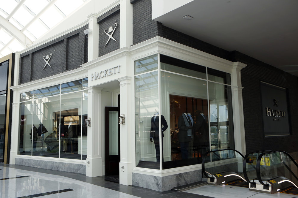 Dark grey brick with the Hacket London logo over the window display and entrance to the British retail store in Woodbury Common Premium Outlet in New York. MEP designed by 2LS.