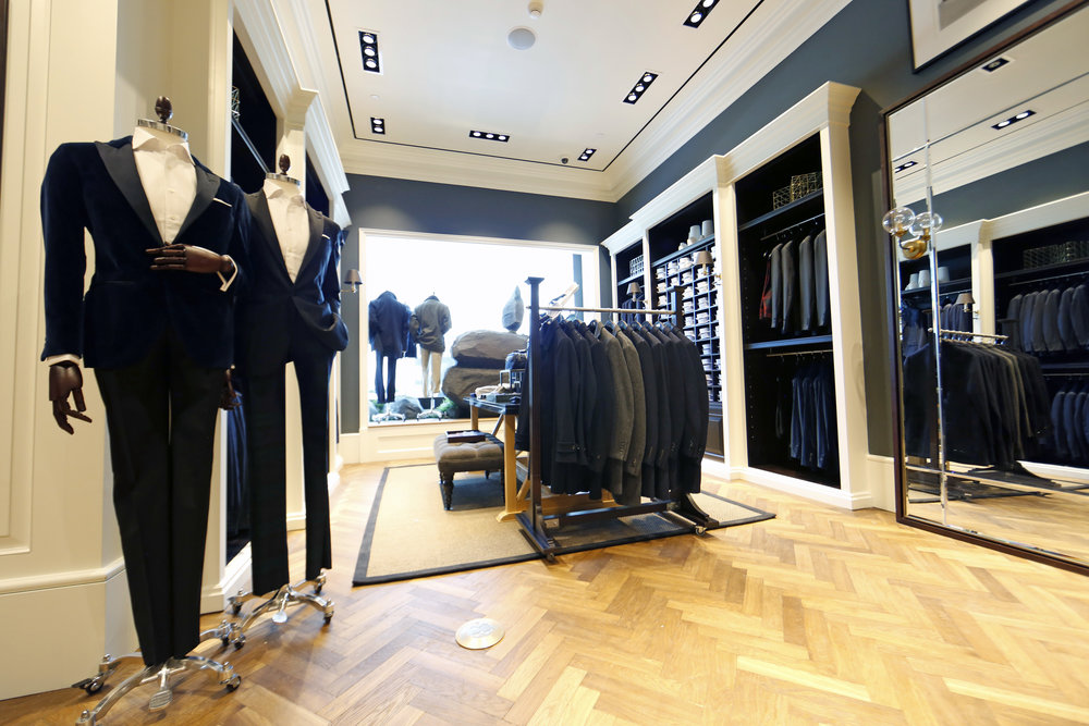 Smartly dressed mannequins in tuxedos on display on fishtail patterned wooden flooring at Hacket London's retail store. MEP by 2LS Consulting Engineering.