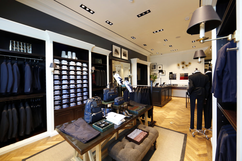 Collared shirts, shoes, dress pants, and bags on display at the center of Hacket London's retail store. MEP designed by 2LS Consulting Engineering.