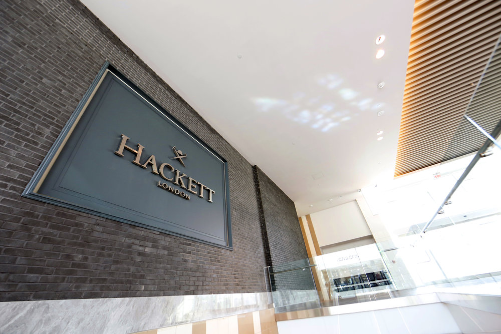 Dark greyish blue exterior signage of Hackett London in Woodbury Common Premium outlet. MEP designed by New York firm, 2LS Consulting Engineering.