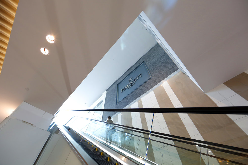A man standing on an escalator beside the exterior signage of Hackett London in Woodbury Common Premium outlet. MEP designed by 2LS Consulting Engineering.