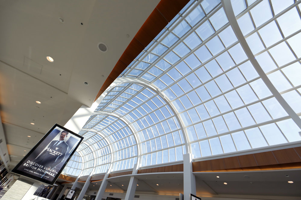 Large windows letting bright sunlight in on the ceiling of Woodbury Common Premium outlet.