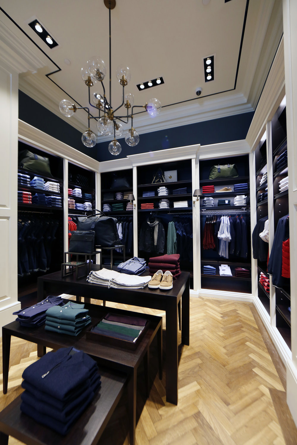 Casual dress shirts and pants on a dark wood display table with tan sneakers and black bags in Hackett London. MEP provided by 2L Engineering.