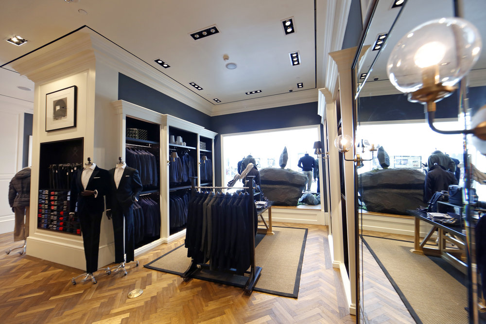 Blazers on display in a retail space with blue accents, white moulding, and wooden flooring at Hackett London, Woodbury Common Premium outlet. MEP by 2LS Consulting Engineering.
