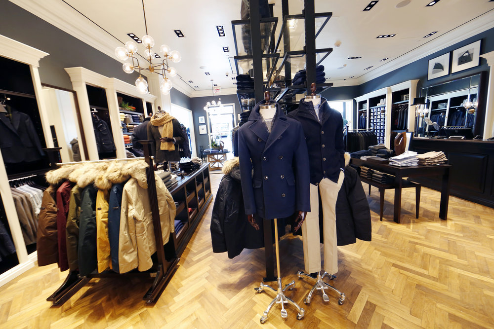 Winter coats on a display rack beside mannequins wearing peacoats in Hackett London, Woodbury Common Premium outlet. MEP designed by 2LS Consulting Engineering.