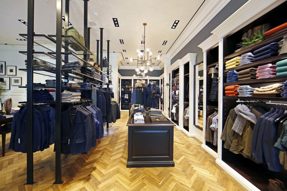 Clothes on display racks and shelves in the midcentury modern interior of Hackett London in Woodbury Common Premium outlet, New York. MEP designed by 2LS Consulting Engineering.