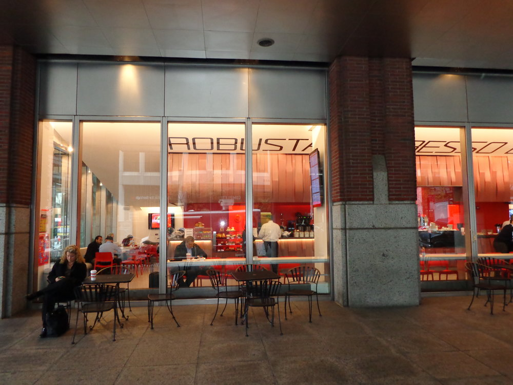 Woman sitting on the outdoor seating area of Robusta Espresso Bar, which can be seen through the large glass windows. MEP provided by 2LS Consulting Engineering.