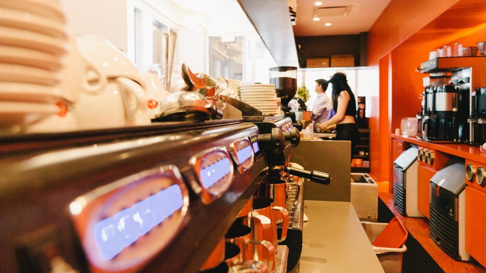 Detail shot of behind the bar, showing the coffee machines, kitchenware and other cafe items at Robusta Espresso Bar. MEP designed by 2L Engineering.