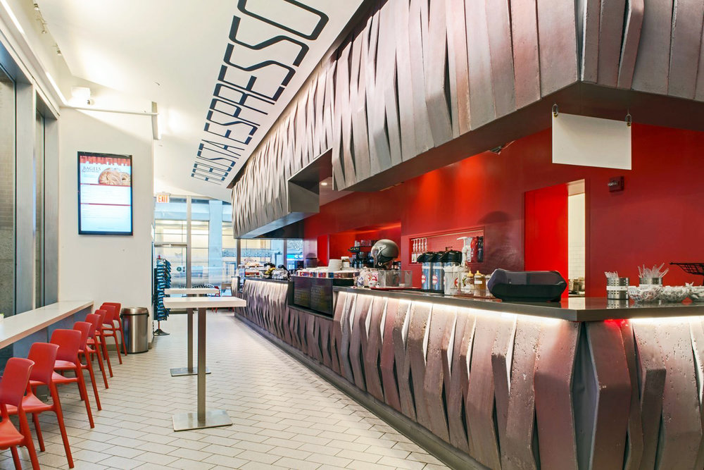 Interior of Robusta Espresso Bar with red seats, and walls with a geometric design on the counters. MEP designed by 2L Engineering.
