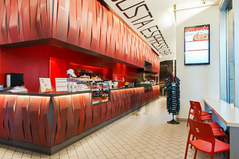 Counter with changing light on a red, brutalist design in Robusta Espress Bar, a cafe with MEP designs provided by 2LS Consulting Engineering, a New York based firm.