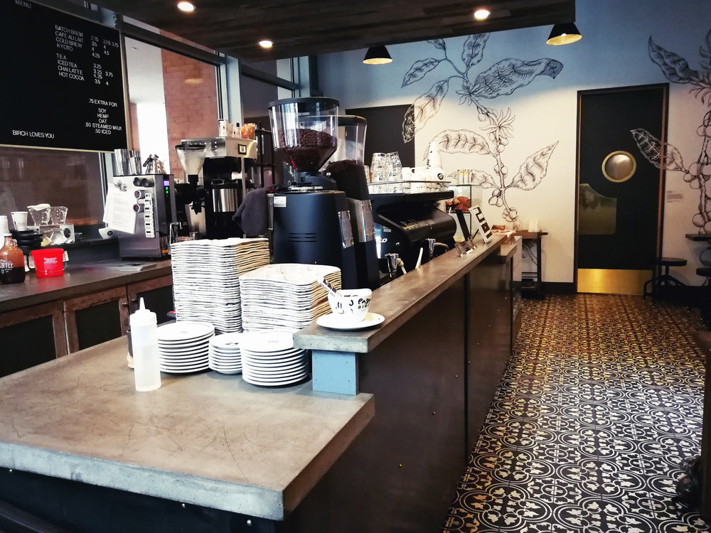 Side view of the Birch Coffee counter with patterned tiles on the floor and plants illustrated on the wall. MEP provided by 2LS Consulting Engineering.