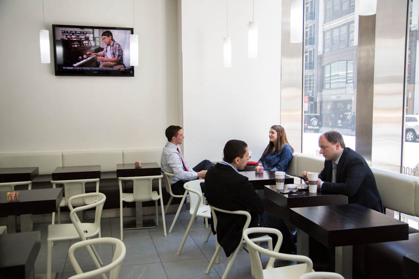 Customers sitting and having coffee as a show plays on a wall mounted TV in Macchiato Espresso Bar, a coffee shop located on Fifth Avenue, New York. MEP by 2L Engineering.