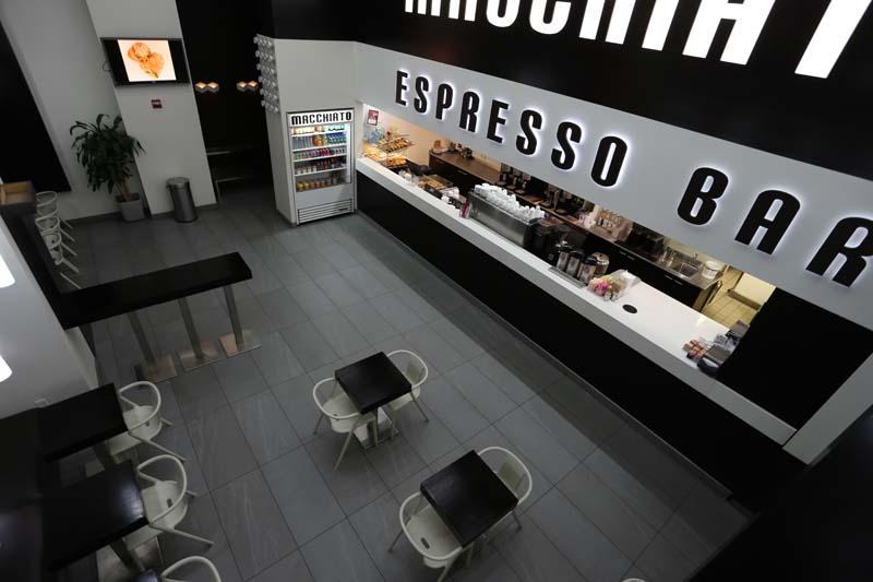Birds eye view of the seating area and bar of Macchiato Espresso Bar, with MEP designed by 2L Engineering.