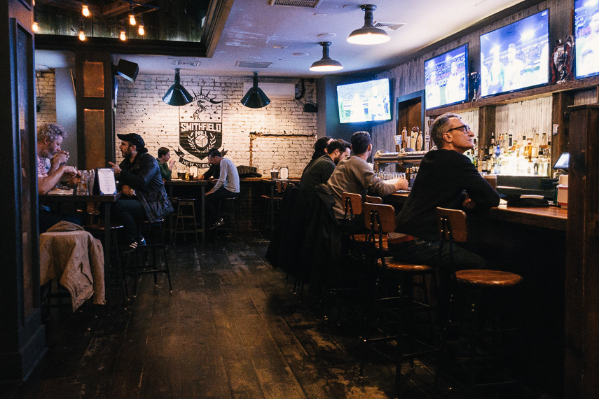People watching sports inside bar, Smithfield Hall, located in New York. MEP provided by 2L Engineering.