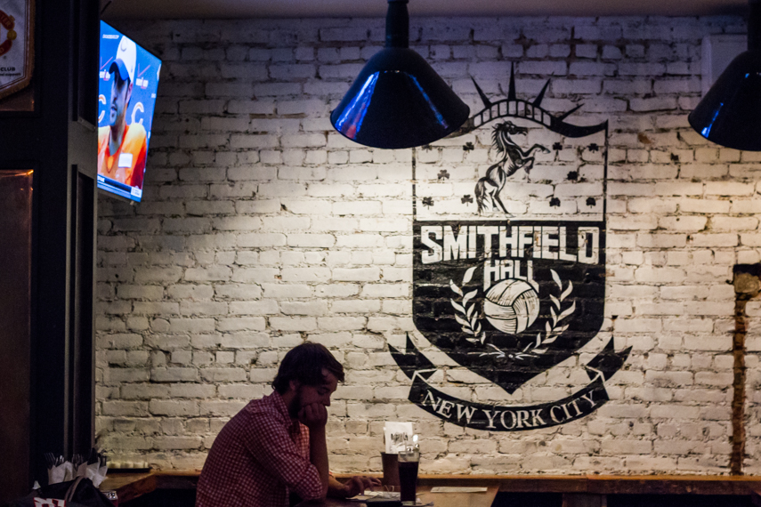 Man sitting with a beer and looking at his phone by a brick wall painted with the Smithfield Hall logo. MEP for Smithfield sports bar designed by 2LS Consulting Engineering.