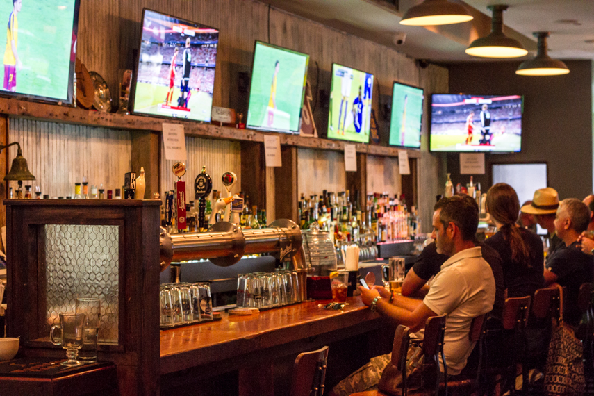 Man checking his phone as football plays on the television screens of a sports bar. Smithfield Hall MEP was designed by 2LS Consulting Engineering.