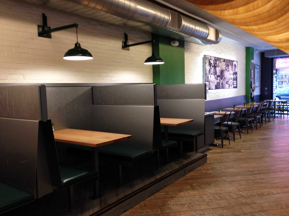 Dark wood booth seating with overhead lighting inside Chop't Salad in the Nolita neighborhood of New York. MEP designed by 2L Engineering.