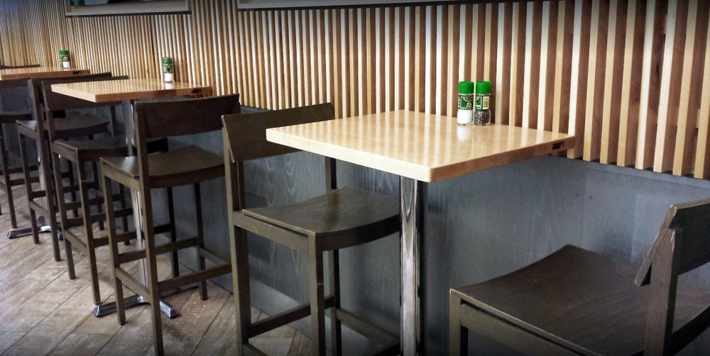 Tall seating area by wooden panelled walls in the Nolita location of Chop't Salad. MEP designed by 2LS Consulting Engineering, a New York based firm.