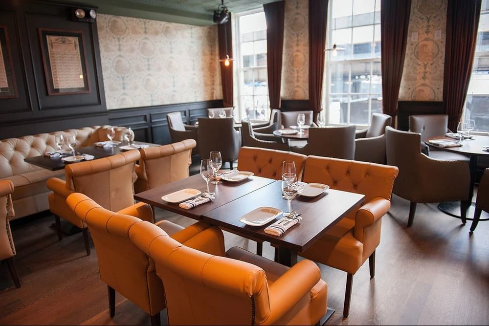 Orange chairs in a transitional designed restaurant, the Trading Post, in New York's Financial District. MEP provided by 2L Engineering.