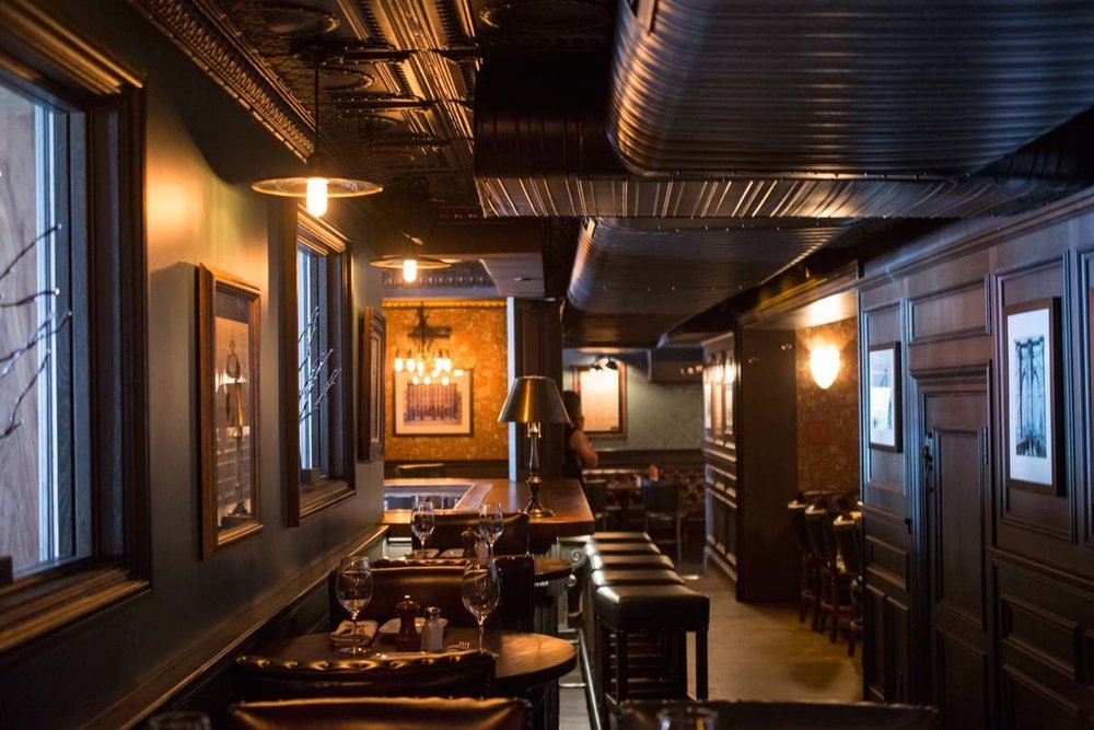 Dimly lit room with dark transitional design in the Trading Post, a bar and restaurant in New York's Financial District. MEP provided by 2L Engineering.
