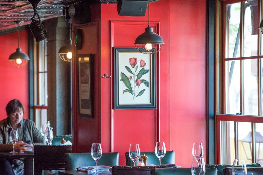 Red painted wall with an illustrated flower on display as a woman enjoys food in the Trading Post, a bar and restaurant located in New York's Financial District. MEP by 2LS Consulting Engineering.