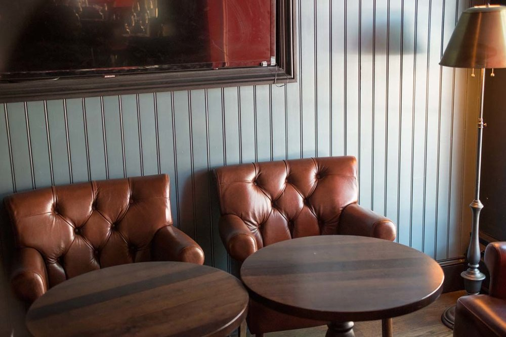 Brown leather seats against a wood panelled wall painted light blue in the Trading Post, a bar and restaurant in New York's Financial District. MEP provided by 2LS Consulting Engineering.