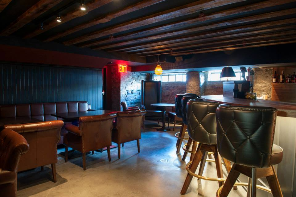 Dark seating area around and by a bar in the basement of the Trading Post, a restaurant with MEP design provided by 2L Engineering.