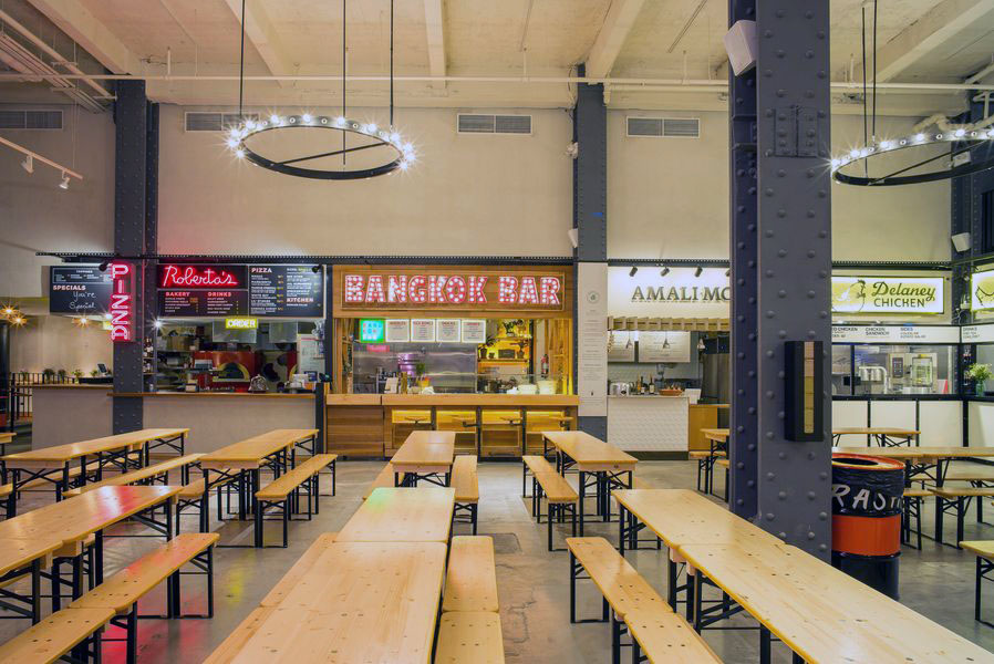 Food hall with wood bench seating in Urbanspace Vanderbilt with the view facing Bangkok Bar, Robusta's Pizza and other eateries. MEP designed by 2L Engineering.