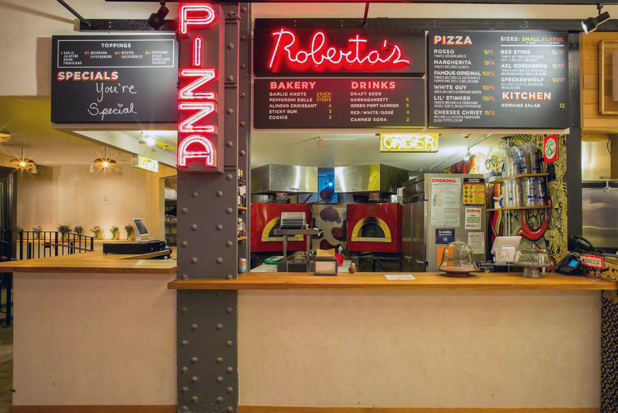 Roberta's Pizza, featuring neon red signs and pizza ovens, in Urbanspace Vanderbilt near Grand Central Terminal. MEP provided by 2LS Consulting Engineering.
