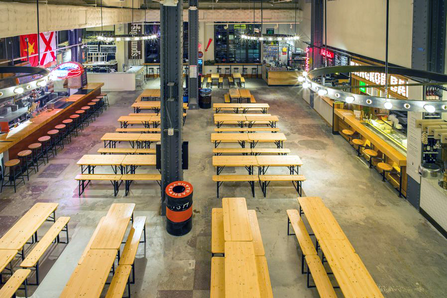 View of the eating area surrounded by food vendors in Urbanspace Vanderbilt, a food hall located near Grand Central Terminal. MEP designed by 2L Engineering.
